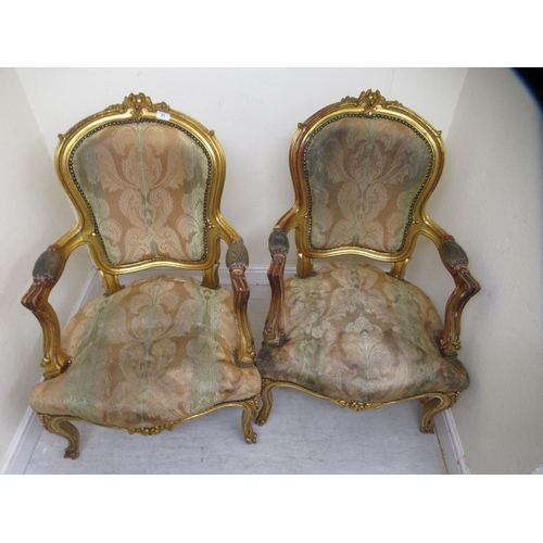 14 - A pair of 20thC Louis XV inspired, giltwood framed and carved, open arm salon chairs, stud upholster...
