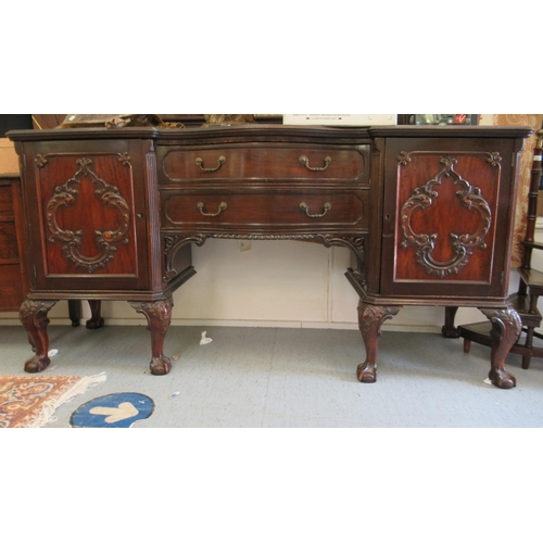 49 - A 1920s mahogany serpentine front sideboard with two central drawers, flanked by two panelled doors,...