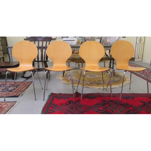 10 - A set of four Janik style light stained and curved plywood, stackable chairs, the one-piece seats an...