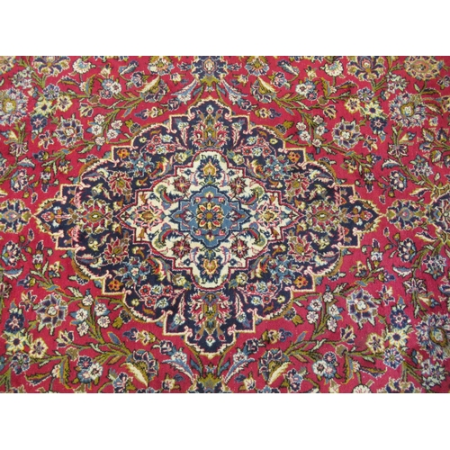 18 - A Keshan carpet, profusely decorated with floral designs in bright colours, on a red ground 120