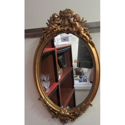 60 - Mirrors: to include an oval example, in a gilded composition frame, surmounted by cherubic figures ...