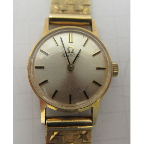 31 - A lady's Omega 9ct gold cased wristwatch, faced by a baton dial, on a 9ct gold flexible strap