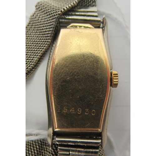 42 - A 1950s 18ct bi-coloured gold cased cocktail watch, faced by an Arabic dial, on a chain mail design ...