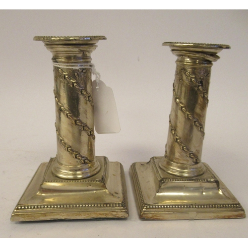 15 - A pair of late Victorian loaded silver cylindrical candlesticks with floral embossed and bead border...