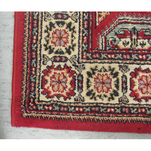 32 - A Persian design rug, decorated with three serpentine outlined, diamond shaped motifs, bordered by s...