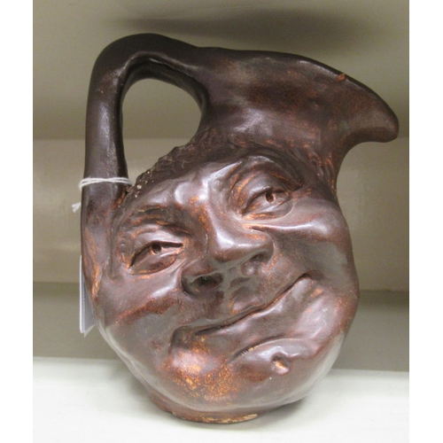 3 - In the manner of Martinware, a ceramic double face jug with an angular handle variously inscri...