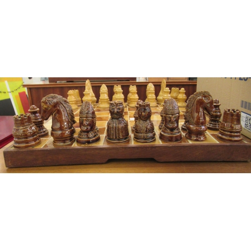 39 - A modern ceramic, two tone tiled chessboard 20''sq with hollow pottery pieces the kings ...