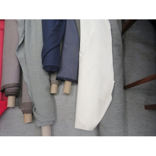 56 - Nine bolts of fabric various colours and lengths