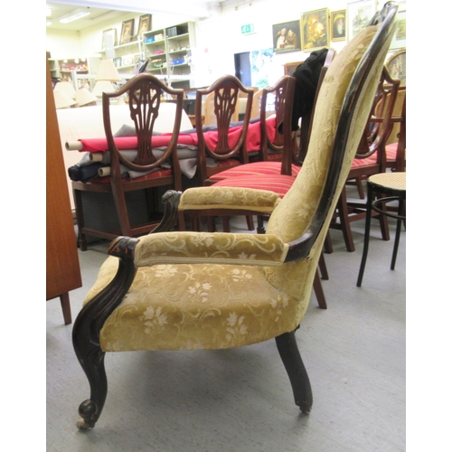 57 - A late Victorian walnut framed spoonback salon chair, upholstered in gold coloured fabric, raised on...