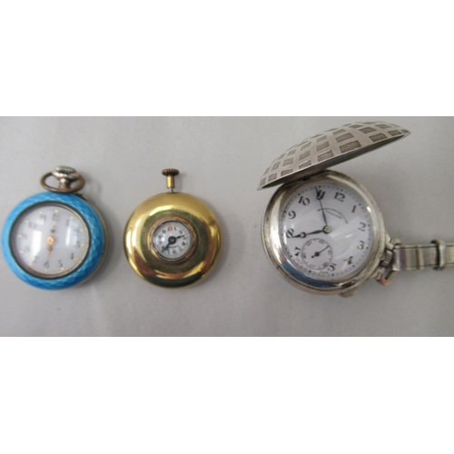 26 - A Mayer Swiss made yellow metal cased watch, faced by an Arabic dial; a ladies engine turned, enamel...