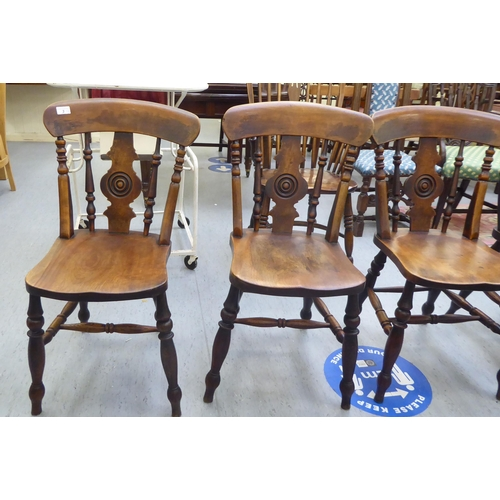 3 - A set of four late Victorian beech and elm framed Windsor chairs, each with a spindled and roundel s...