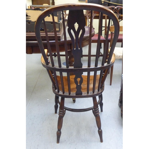 6 - A 19thC Windsor beech and elm framed high hoop, spindled and splat back arm chair, the solid seat ra...