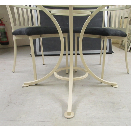 110 - A modern cream painted metal table with a glass top, raised on splayed legs 30