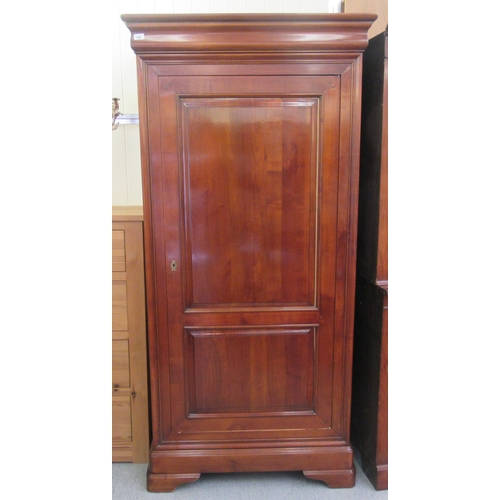 148 - A modern cherrywood armoire with a moulded cornice, over a full height, twin panelled door, raised o...