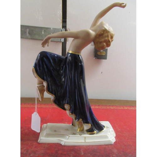 165 - A Royal Dux gilded and painted porcelain dancer, wearing a midnight blue skirt, on a plinth bears p...
