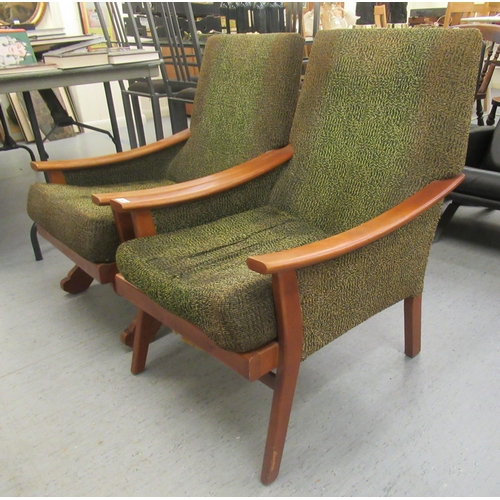 251 - Two similar 1970s stained beech framed chairs with enclosed fabric arms, raised on splayed legs