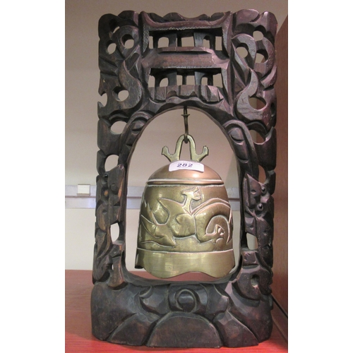 282 - A 20thC Chinese cast bronze table bell, in a carved hardwood frame 12