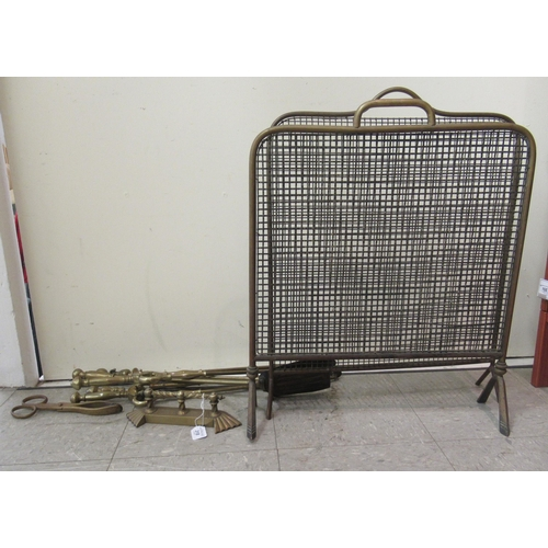 318 - An Edwardian three piece brass fireside companion, two pokers and two similar, freestanding brass fr...