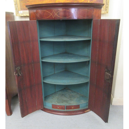 336 - A George III satinwood and ebony inlaid mahogany quadrant corner cupboard with two panelled doors on...