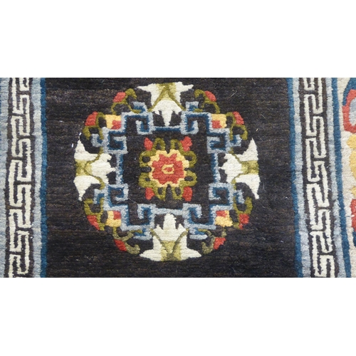 369 - A woollen carpet, decorated with floral and Greek key designs, on a black ground 68