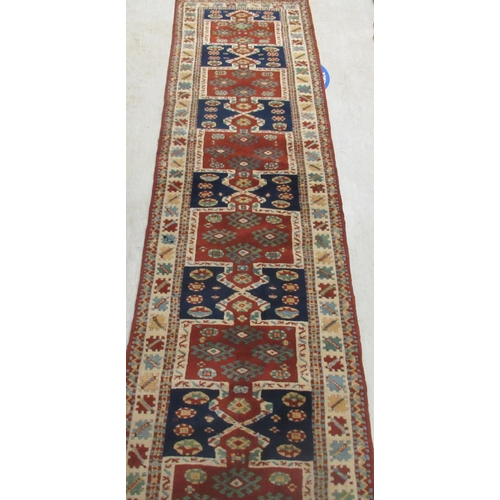 5 - A Persian runner, decorated with repeating stylised designs, on a multi-coloured ground 22