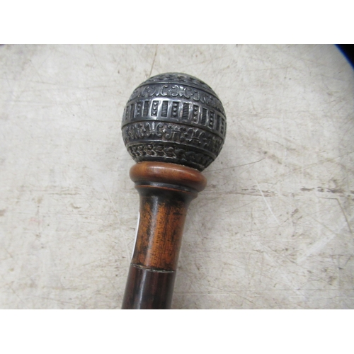 70 - A late 19thCfruitwood walking cane with a white metal ball finial