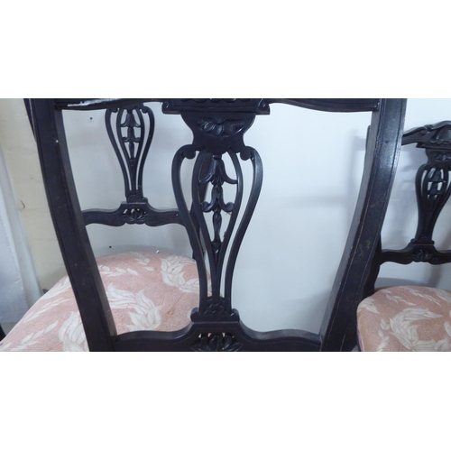 348 - A set of four late Victorian ebonised salon chairs, each with a vase shaped splat, raised on cabriol...