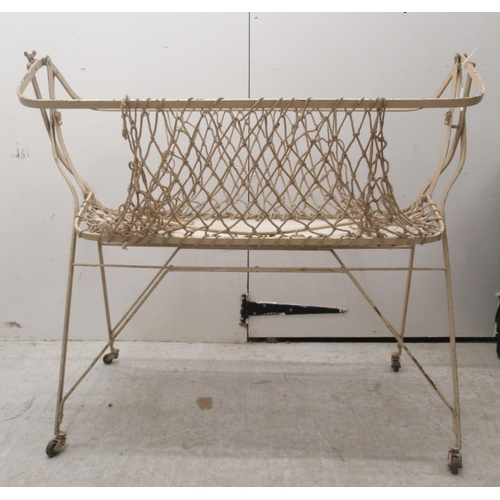 113 - A late Victorian/Edwardian baby's cream painted wrought iron framed folding cot, incorporating a str...