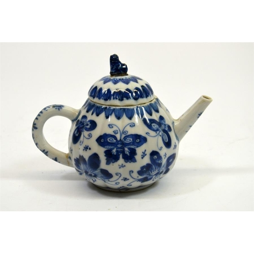 11 - A small Chinese blue and white teapot, 18th century, decorated with butterflies, 11cm high...