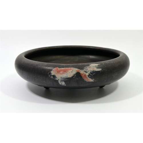 29 - A Japanese burnished blackware bowl, on three feet, painted with goldfish and seaweed, impressed mar...