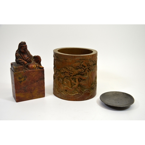 39 - A Chinese bamboo brush pot, cylindrically formed and carved with figures in a wooded landscape, and ...