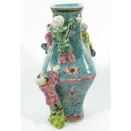 11A - An Oriental vase, square section lozenge form relief moulded with acrobatic boys, 22cm high...