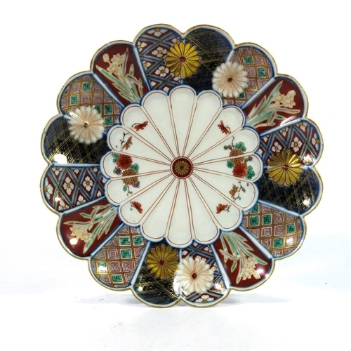 12 - A Japanese Imari plate, Meiji, double scalloped rosette form with geometric panels and floral specim...