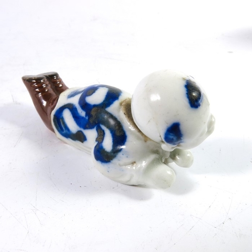 24 - An Oriental novelty articulated porcelain figure of a boy, the head and tongue moving, 9cm long...
