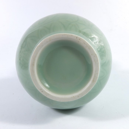 25 - A Chinese celadon double gourd vase, relief moulded with floral design, 22cm high...