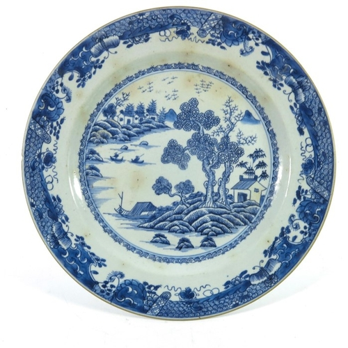 29 - A Chinese export blue and white plate, 18th century, painted with a watery landscape, possibly Nanki...