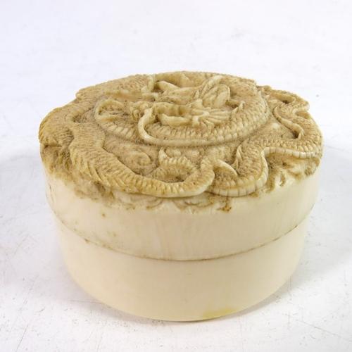 30 - λ A 19th century Oriental carved ivory box, cylindrical form, the lid with an entwined dragon in low...