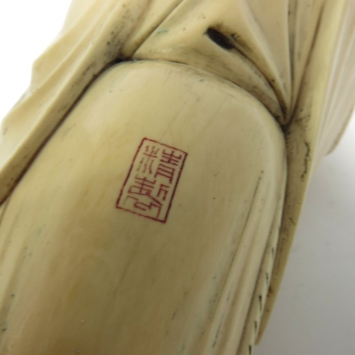 32 - λ A 19th century Chinese ivory figure, modelled as an Elder with peony and staff, 31cm long...
