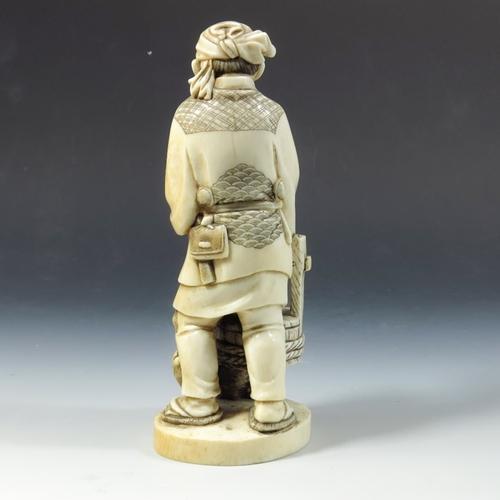 33 - λ A 19th century Japanese ivory okimono, Meiji, modelled as a man with basket and a dog under, 19cm ...