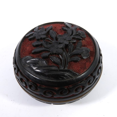 34 - A Chinese cinnabar lacquer enamel box, with decorated lid depicting flowers, diameter 6.5cm...