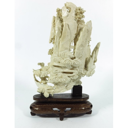 37A - λ A 19th century carved ivory figure group of Buddha and deities infront of a rocky landscape, on st...