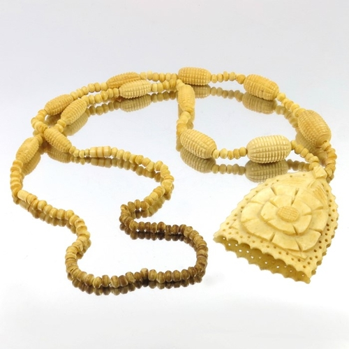 38 - A 19th century carved bone necklace, the pierced pendant with central flower, 72cm long...