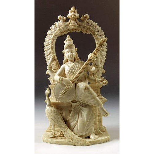 40 - λ A 19th century Indian ivory figure of Saraswati, the Hindu deity, modelled playing the sitar, with...