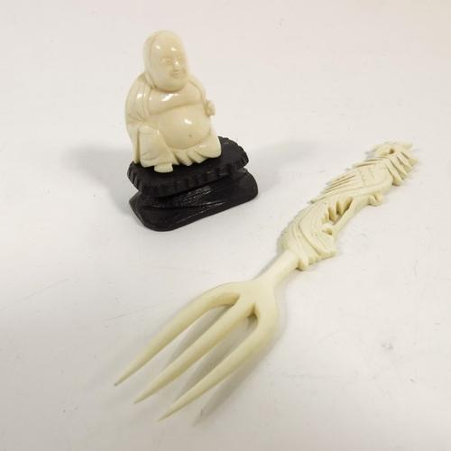 43 - λ A 19th century Japanese ivory okimono, modelled as a sitting Buddha, together with a Chinese fork,...