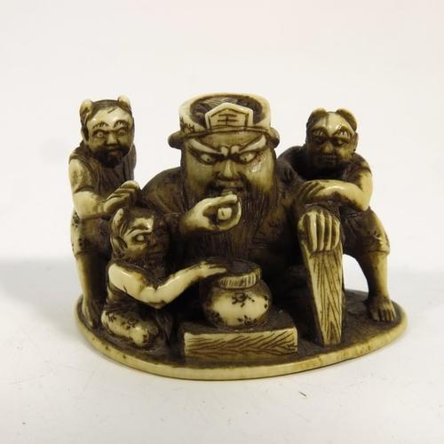 44 - λ A 19th century Japanese ivory netsuke, Meiji, modelled as a figure group with man and horned imps,...