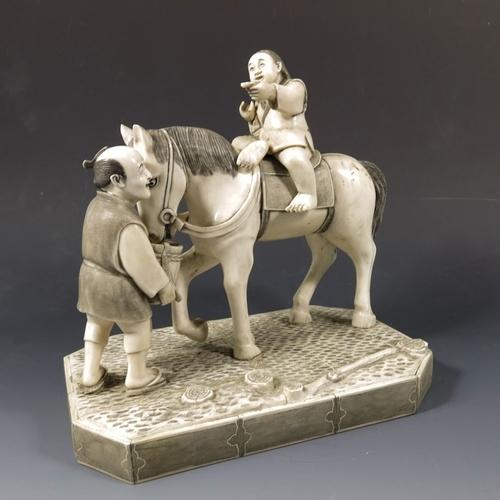 45 - λ A 19th century Japanese ivory okimono, Meiji, modelled as a boy on a horse with old man, 22cm high...