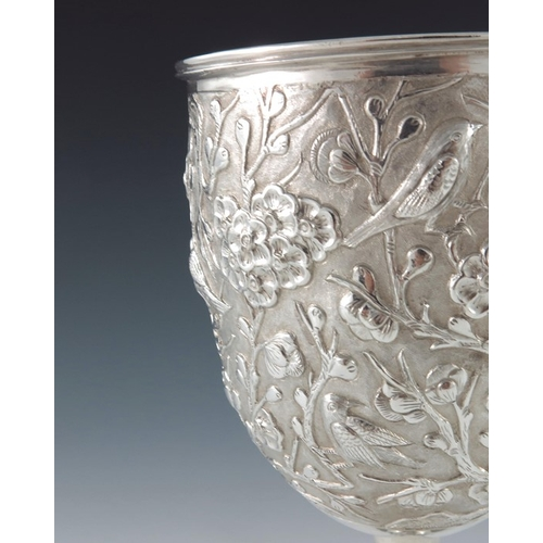 5 - A Chinese white metal goblet, circa 1900, repousse decorated and chased with prunus trees and birds,...