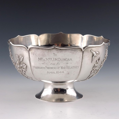 6 - A Chinese white metal bowl, ogee arcaded lobed form, on splayed foot, cast with prunus and wildlower...