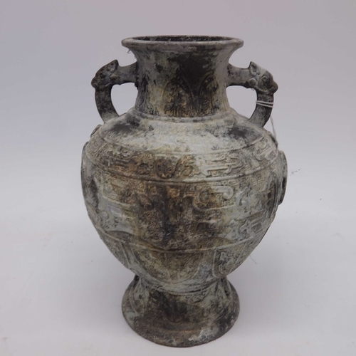 28 - An Archaistic style cast metal footed vase, twin handled baluster form, decorated with moulded shiel...