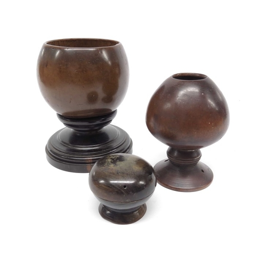 34 - A coconut cup on turned wooden base, a turned wooden footed ovoid cup and a turned wooden pot and co...
